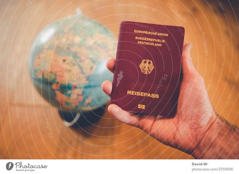 Weltreise - Mann hält Reisepass in der Hand mit Globus im Hintergrund Urlaub weltreise verreisen Mensch Urlaubsstimmung Ausweis Tourismus