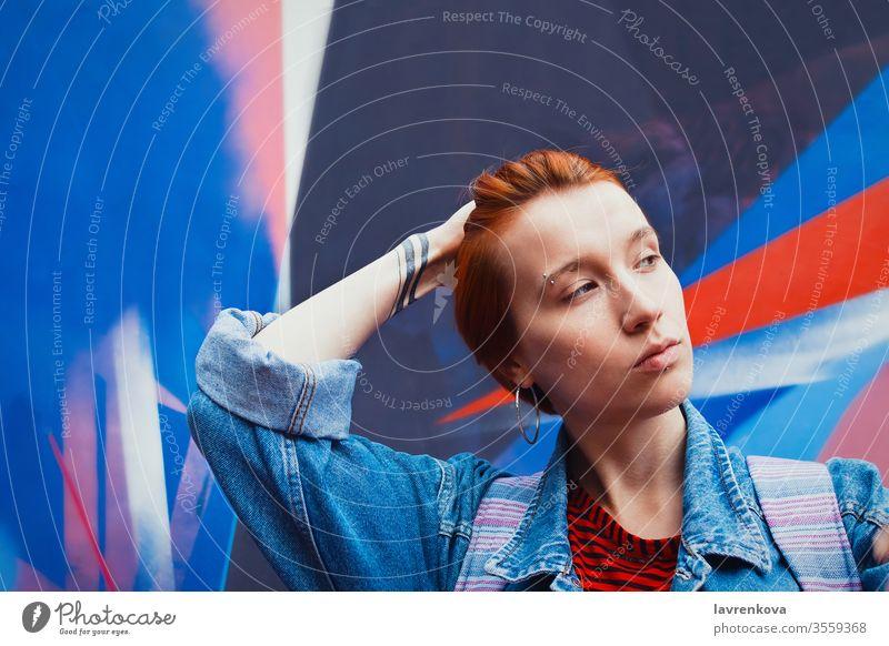 Junge erwachsene weiße Frau in Jeansjacke mit abgestorbenen roten Haaren flacht ihr Haar ab, Lifestyle-Porträt mit selektivem Fokus Jacke Jeanshose Model Straße