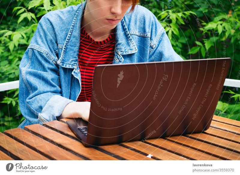 Nahaufnahme-Porträt einer jungen erwachsenen Freiberuflerin, die draußen an ihrem Laptop arbeitet Schüler online Job Erwachsener Sitzen Frau im Freien Internet
