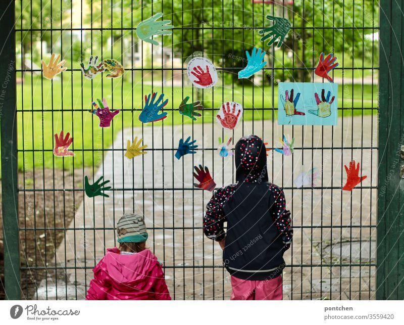 Zwei kleine weibliche Kinder in regenbekleidung stehen vor dem gartentor eines Kindergartens und blicken hinein. Am Tor hängen bunte gebastelte Hände. Sehnsucht, vermissen. Schließung