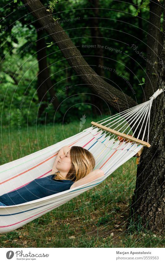 Junge Frau entspannt sich in der Hängematte in der Natur Erwachsener allein Hinterhof Windstille sorgenfrei lässig bequem Landschaft Tag träumen leicht genießen