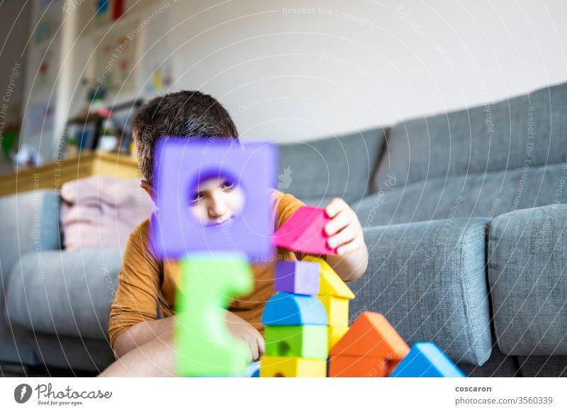 Lustiger Junge spielt zu Hause mit Blöcken Aktivität bezaubernd Baby schön Schlafzimmer Klotz Baustein bauen Kaukasier Kind Kindheit Farbe farbenfroh