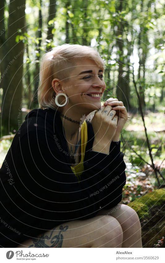 Portrait einer jungen Frau mit Piercings, Tätowierungen und Tunnel Mädchen blond Schmuck Assecoires Shirt Hemd schön draussen schauen beaobachten gelb Hand