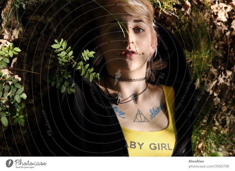 Portrait einer jungen Frau mit Piercings, Tätowierungen und Tunnel, die auf dem Waldboden liegt Mädchen blond Schmuck Assecoires Shirt Hemd schön draussen