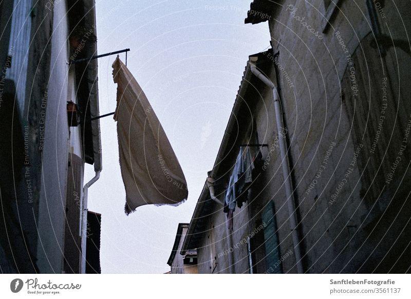 Wäsche im Wind Sommer Dämmerung Südfrankreich Menschenleer Außenaufnahme Waschtag trocknen hängen Straße Farbfoto Hinterhof Frische Häusliches Leben Tag Luft