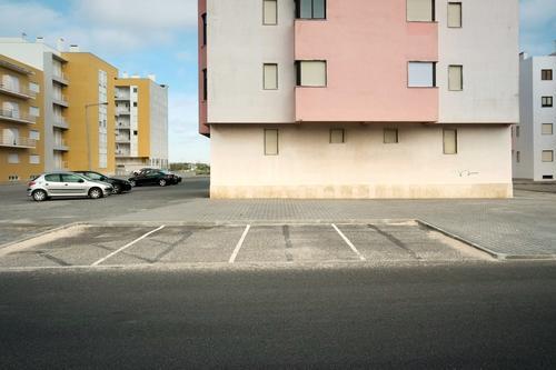 Siedlung Vorort Stadt Wohnungen wohnen beton parken autos parkplatz siedlung dorf Architektur fenster gebäude menschenleer tist grau Außenaufnahme Fassade