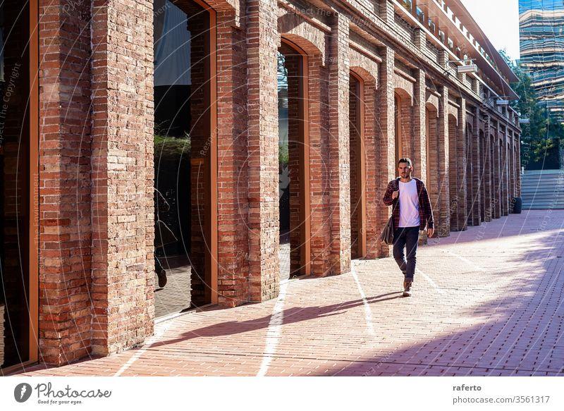 Bärtiger junger Mann mit Umhängetasche beim Spaziergang in einem Geschäftsviertel Erwachsener Beteiligung junger Erwachsener im Freien Menschen Business