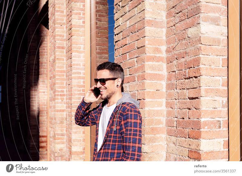 Junger bärtiger Mann, der mit Sonnenbrille an einer gemauerten Wand lehnt, während er im Freien ein Smartphone benutzt. Person Telefon 1 männlich Mitteilung