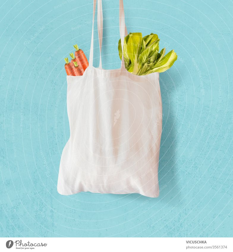 Weiße Textil-Einkaufstasche mit Gemüse auf hellblauem Hintergrund. Null-Abfall.  Wiederverwendbar. Umweltfreundlich keine Verschwendung weiß