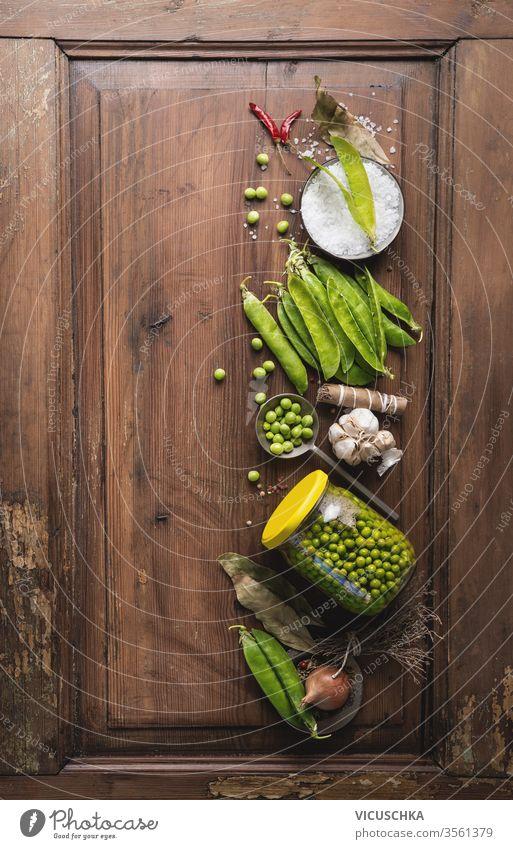 Frische Gartenerbsen in Dosen im Glas mit Gewürzen auf einem rustikalen Holztisch, Draufsicht. Einmachen der Gemüseernte. Erbsen Konservenherstellung Vegetarier