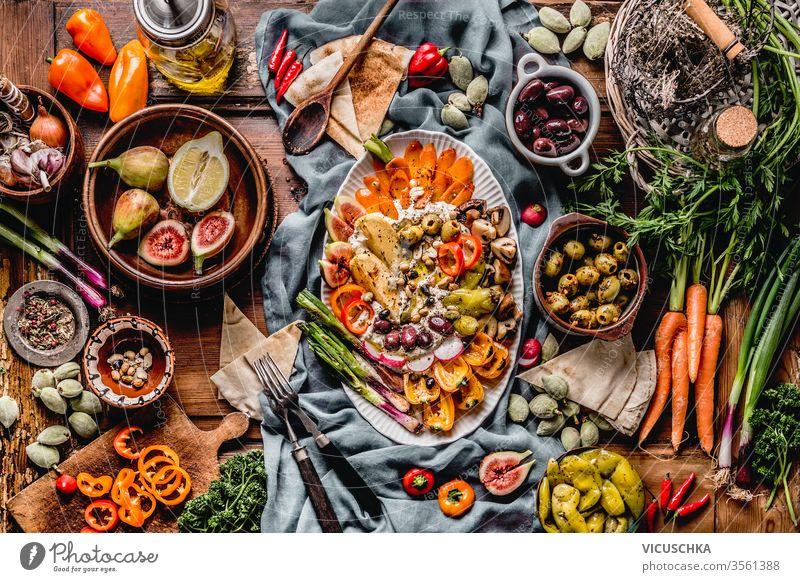 Schmackhafte mediterrane Küche mit Hummus-Platte. Ramadan-Iftar-Abendessen. Verschiedene eingelegte und frische Gemüse: Oliven, Fide, grüne Mandeln. Veganes Party-Essen . Festliche Versammlung
