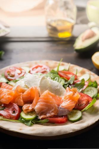 Schmackhafter Wrap mit Lachs.  Nahaufnahme. Konzept der gesunden Ernährung. geschmackvoll umhüllen Brot Käse Rucola Tomaten Gurken Fladenbrot Zutaten hölzern