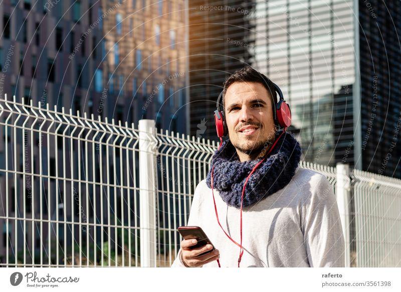 Junger bärtiger Mann mit Kopfhörern und Smartphone in der Hand, während er an sonnigen Tagen gegen Wolkenkratzer läuft Person Straße im Freien Telefon