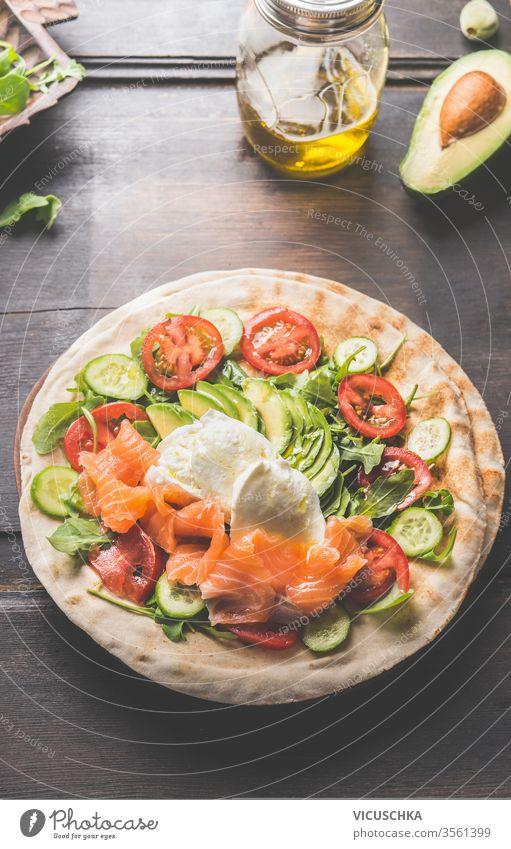 Tortilla mit Lachs, Avocado, Käse, Rucola, Tomaten und Gurken. Fladenbrot mit Zutaten . Wrap Vorbereitung. hölzern Tisch umhüllen Draufsicht abschließen