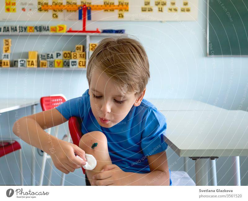 Ein Junge mit einem gebrochenen Knie schlägt auf die Wunde. Verletzte Kinder, Krankenversicherung, Erste Hilfe, Kinderbetreuung, Konzept des Erwachsenwerdens.