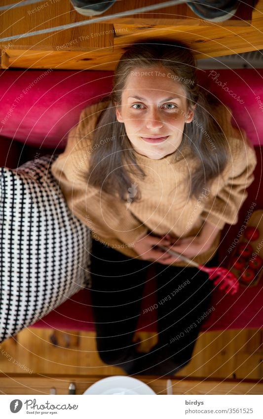 Junge Frau auf rotem Sofa sitzend blickt lächelnd nach oben in die Kamera Blick in die Kamera rotes Sofa Esstisch Hunger Gesicht feminin schön Porträt