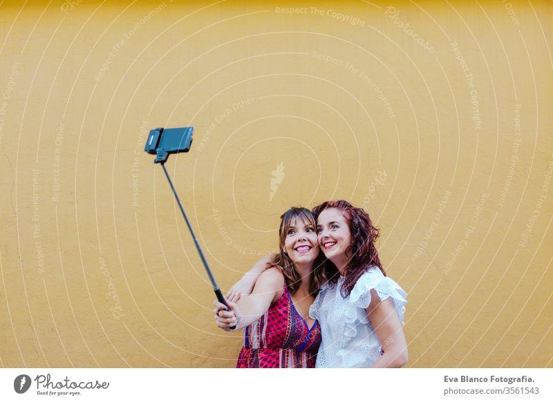 zwei Freundinnen oder Schwestern, die ein Foto im Freien mit einem Mobiltelefon über gelbem Hintergrund machen. technologie- und lebensstilkonzept Freunde Handy