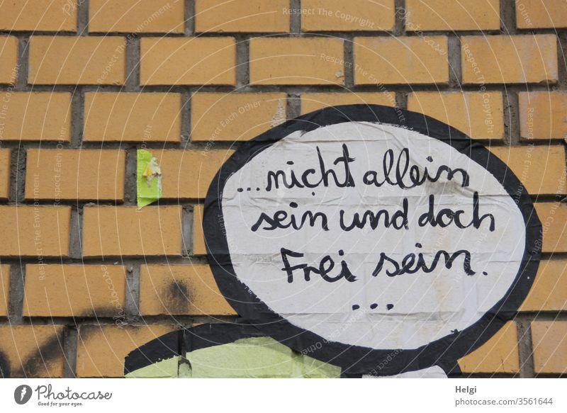 nicht allein sein und doch frei sein - geschrieben in schwarzer Schrift auf weißem Grund in Sprechblase an einer Klinkerwand Spruch Wunsch Wand Außenaufnahme
