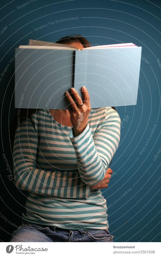Frau mit Buch lesen Lesen eines Buches blau geringelt Ringelpulli haltend Lektüre
