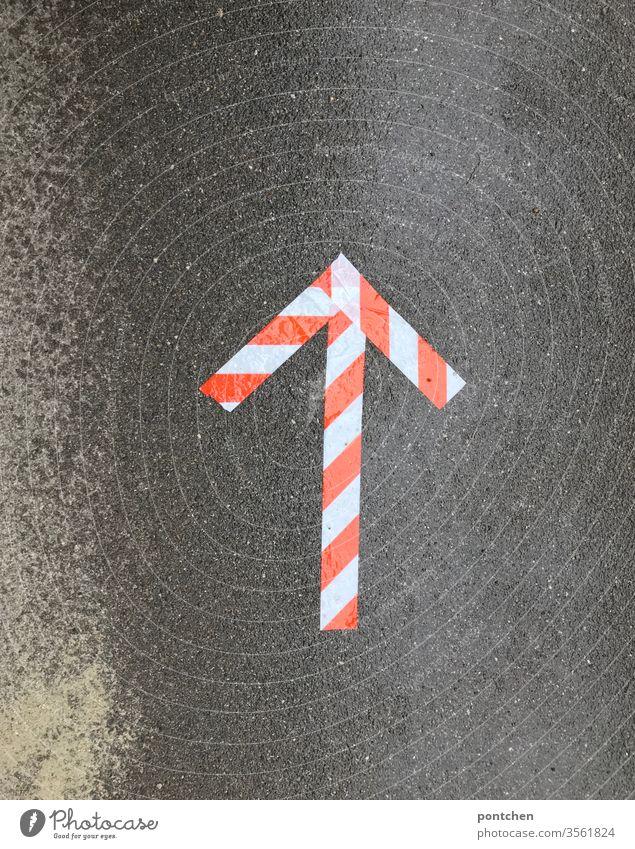 Orientierung. Ein Pfeil aus rot-weißem Kleband weist den Weg auf nasser Asphalt wegweiser klebeband richtung Schilder & Markierungen Zeichen Navigation