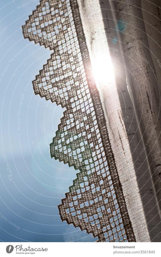 Gardine mit Häkelborte im Gegenlicht Zickzack Sonnenlicht Stoff Textilien gehäkelt verzierung