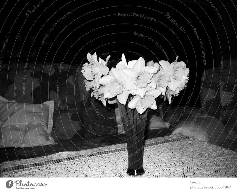 Sie war nicht mehr da, und doch hatte er eine Vase mit Osterglocken auf den Couchtisch gestellt. Wohnzimmer Blumen Frühling Tisch Blumenstrauß Innenaufnahme