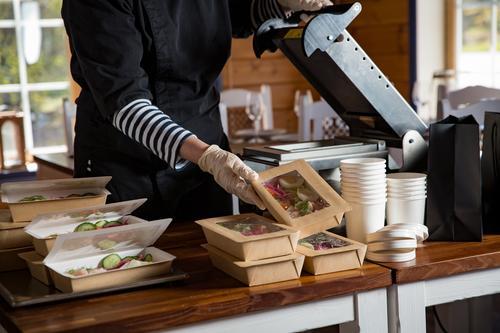 Restaurantmitarbeiter mit Schutzmaske und Handschuhen, die in Lebensmittelkartons verpacktes Essen zum Mitnehmen verpacken. Lebensmittellieferdienste und kontaktloser Online-Einkauf von Lebensmitteln.