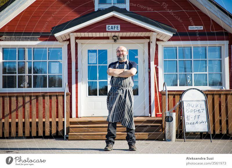 Porträt eines selbstbewussten reifen Mannes mit Bart, Restaurantangestellter mit Schürze vor dem Restaurant stehend. Konzept eines Kleinunternehmens. Waffen