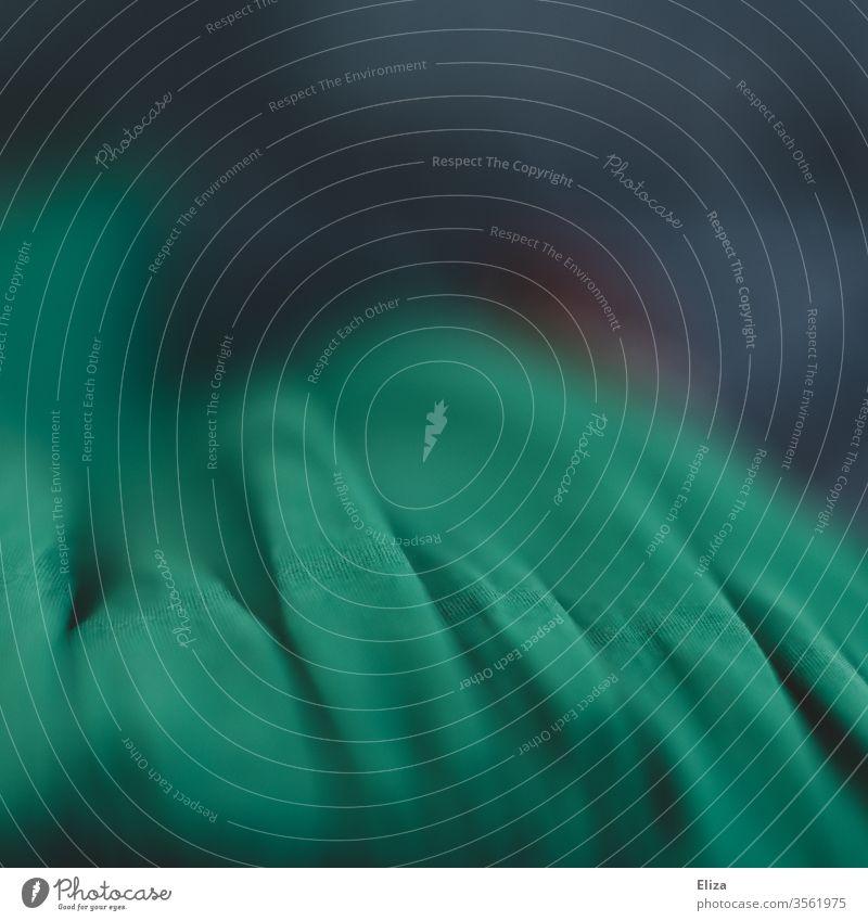 Nahaufnahme eines grünen Stoffes mit viel Unschärfe Makro abstrakt Schärfeverlauf Detailaufnahme Material Textur Textil Bekleidung Mode Struktur Falten Wellen