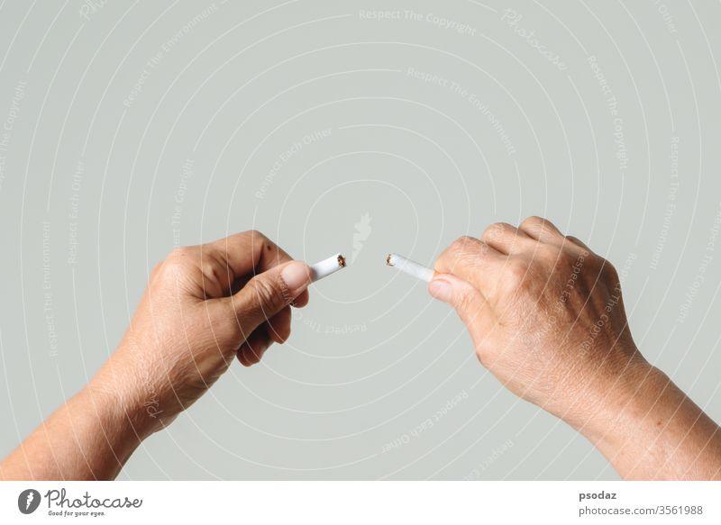 Raucherentwöhnung, kein Tabaktag, Mutterhände brechen die Zigarette Süchtige Erwachsener gealtert Anti Hintergrund schlecht gebrochen Pflege Kaukasier