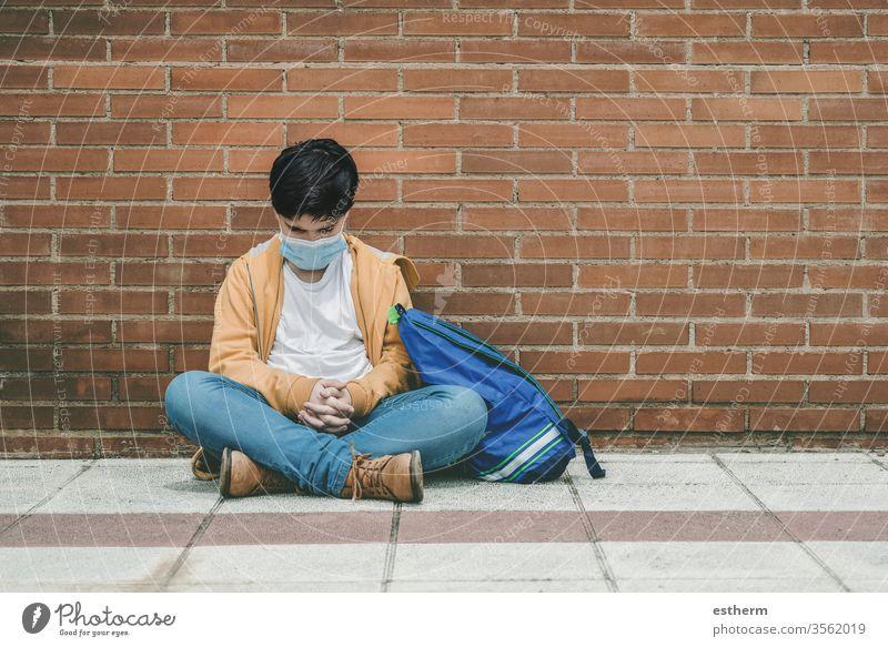 trauriges Kind mit medizinischer Maske und Rucksack Coronavirus Virus Seuche covid-19 Schule Schüler Pandemie Quarantäne Großstadt Schuljunge Traurigkeit