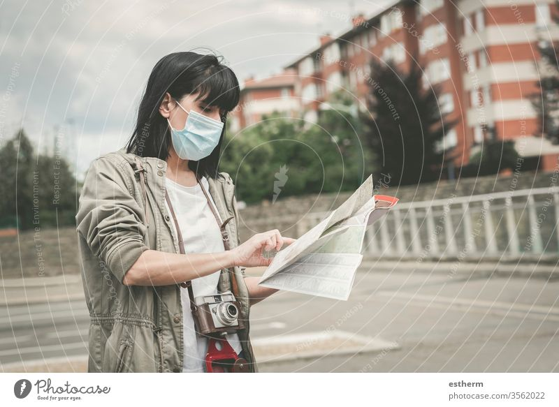 Frau mit medizinischer Maske, die mit einer Kamera auf einen Stadtplan schaut Coronavirus Junge Frau Virus Seuche Reisender reisend Tourist Tourismus Feiertage