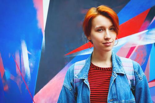 Junge erwachsene weiße Frau in Jeansjacke mit abgestorbenen roten Haaren, Lifestyle-Porträt mit selektivem Fokus Erwachsener attraktiv lässig Kaukasier gefärbt