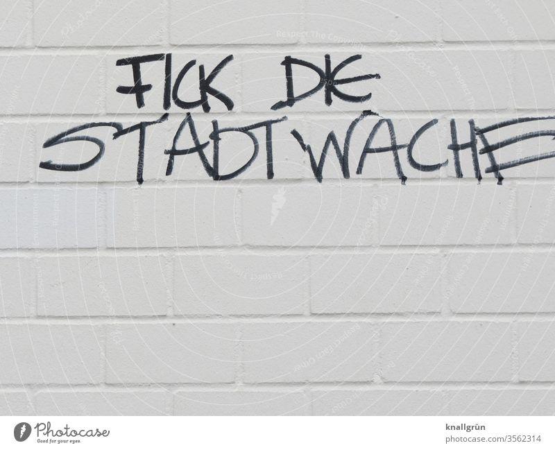 """Schwarzes Graffiti """"FICK DIE STADTWACHE"""" auf weisser Hauswand Polizei Aggression Frustration Ärger Wut Wand Hass Feindseligkeit Buchstaben Wort Satz"""