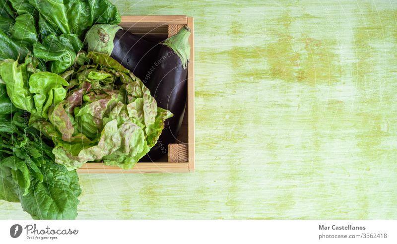 Holzkiste mit Gemüse auf grünem Holzsockel. Platz zum Kopieren. Konzept Gemüse. Veganer Holzschachtel grüner Hintergrund Gemüsekiste Kasten Aubergine Salat