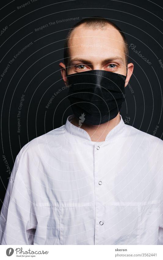 junger Arzt mit kurzen Haaren im Ärztekittel trägt eine schwarze Schutzmaske. männlicher Laborant im Schutzanzug bei der Arbeit mit Patienten mit Coronavirusinfektion während der Pandemie.