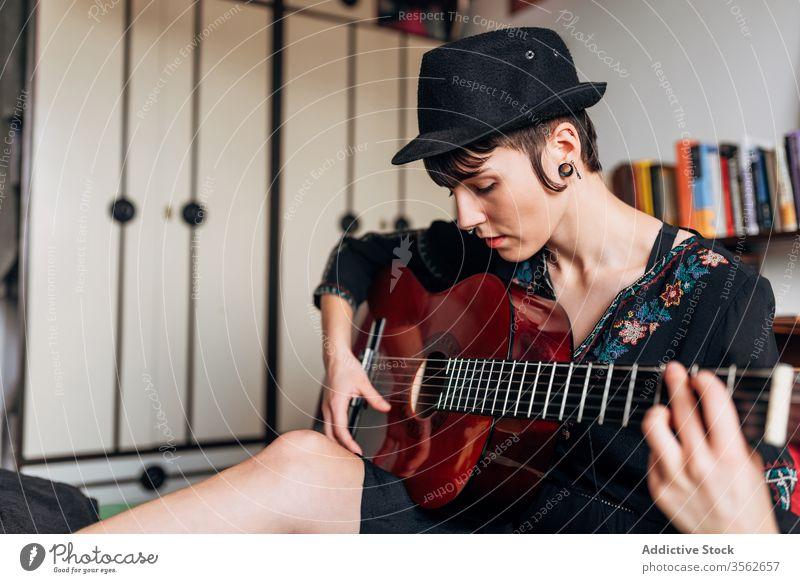 Ruhige Frau spielt Gitarre im Schlafzimmer spielen Musik akustisch Instrument Windstille ruhig trendy Melodie Klang Bett sitzen Hobby Musiker Gesang