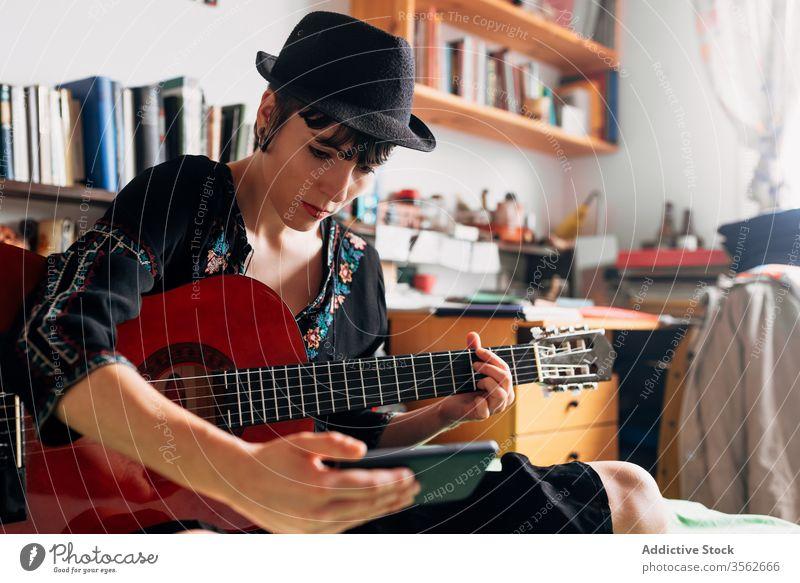 Frau mit Gitarre schaut zu Hause auf Smartphone Browsen akustisch trendy Nachricht benutzend Funktelefon Musik Wochenende Stil anhaben Hut Bett sitzen