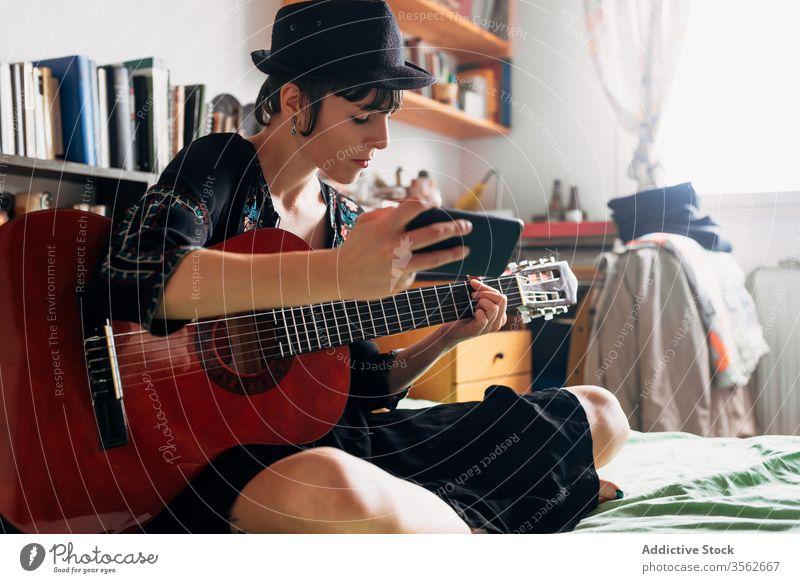 Frau mit Gitarre und Smartphone zu Hause Browsen akustisch trendy Nachricht benutzend Funktelefon Musik Wochenende Stil anhaben Hut Bett sitzen