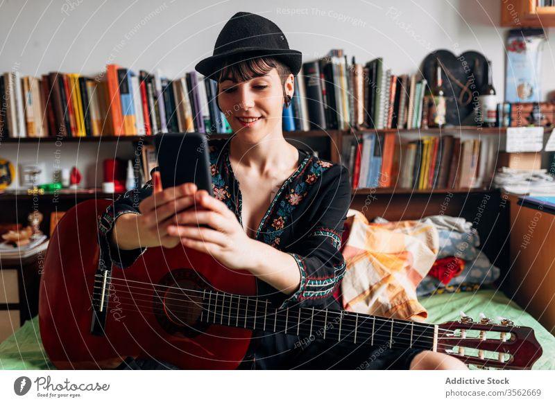 Fröhliche Frau mit Gitarre surft auf Smartphone zu Hause Browsen akustisch trendy Nachricht benutzend Funktelefon Musik Wochenende Stil anhaben Hut Bett sitzen