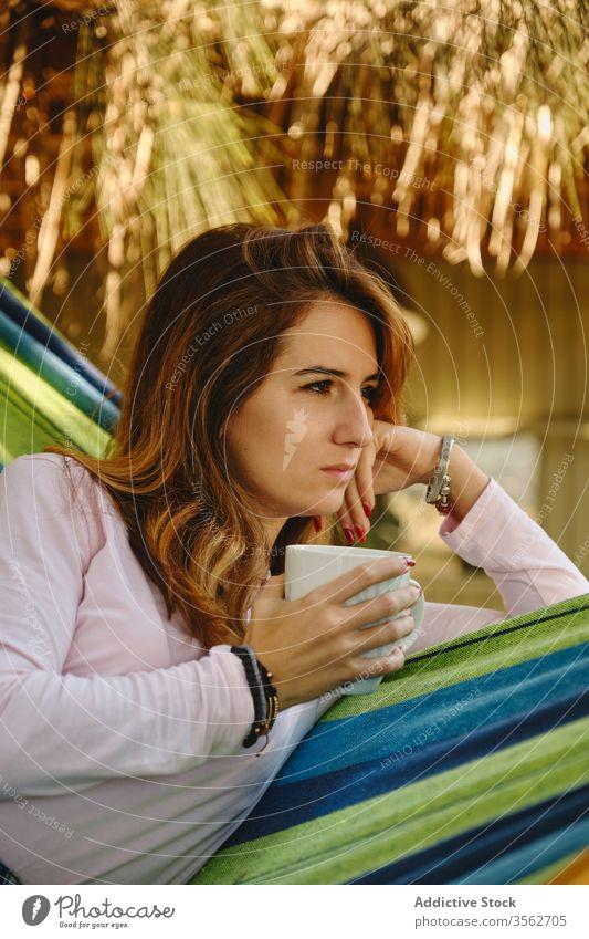 Entspannte Frau mit Tasse Kaffee in Hängematte sich[Akk] entspannen Heißgetränk Windstille Lügen Barfuß Hof genießen Sommer Feiertag Urlaub Wochenende Becher