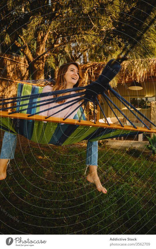 Entspannte Frau in Hängematte im Sonnenuntergang sich[Akk] entspannen Windstille Lächeln Glück Lügen Hof genießen Sommer Feiertag Urlaub Wochenende lässig