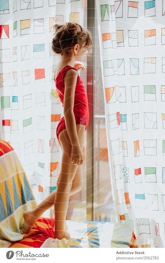 Kleines Mädchen schaut aus dem Fenster heimwärts Sofa Gardine ruhen stehen Body farbenfroh hell gemütlich Lifestyle Raum Komfort Appartement