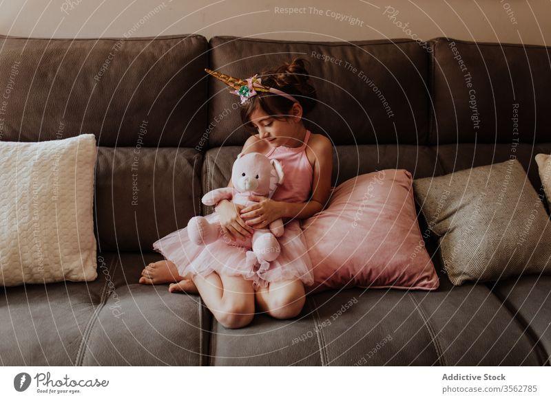 Kleines Einhorn-Knuddelspielzeug auf dem Sofa Mädchen Spielzeug Umarmung heimwärts ruhen Zauberei u. Magie Tracht Wochenende Kind sich[Akk] entspannen gemütlich