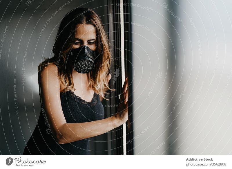 Junge Frau mit Atemschutzmaske steht an Glaswand Mundschutz Isolation COVID Coronavirus Konzept verhindern Schloss Selektiver Fokus behüten einlochen traurig