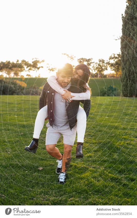 Glückliches Paar amüsiert sich auf der grünen Wiese Huckepack Zusammensein Liebe Feld Gras Spaß haben Partnerschaft Park positiv heiter jung Natur Bonden