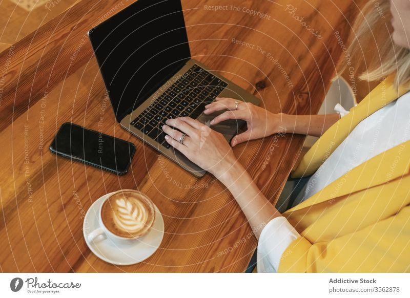 Erwachsene Frau trinkt aromatischen Kaffee, während sie im Café am Laptop arbeitet freiberuflich benutzend schäumen Internet Latte trinken Tasse heimwärts