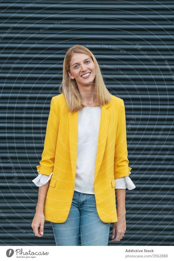 Fröhliche, stilvolle Frau auf der Straße Jacke Lächeln Freude Mode Outfit blond Glück Jeanshose charmant zufrieden freiberuflich Stil Bekleidung heiter trendy