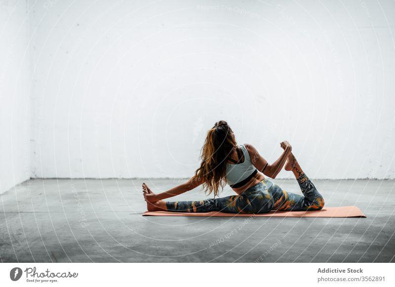 Schlanke Frau praktiziert Yoga auf Matte üben Frontspalte Split hanumanasana Pose schlank Unterlage beweglich Asana sitzen Stock Sportbekleidung aktive Kleidung