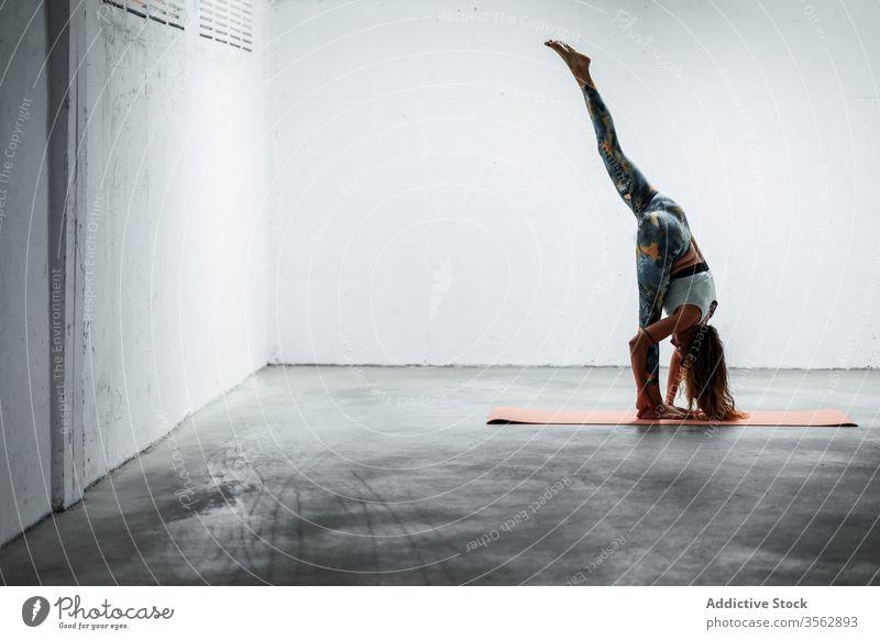 Ruhige Frau beim Stehen auf der Matte gespalten Yoga Stehende Teilung Split üben beweglich Unterlage Gleichgewicht ruhig Harmonie Windstille Pose schlanke Asana